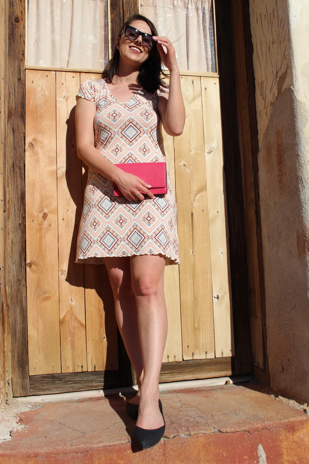 This is a close up of me wearing a geometric white dress with many colors, holding a Coach clutch.