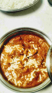 Serving garnished with cheese chicken lababdar in a bowl with steam rice for chicken lababdar recipe