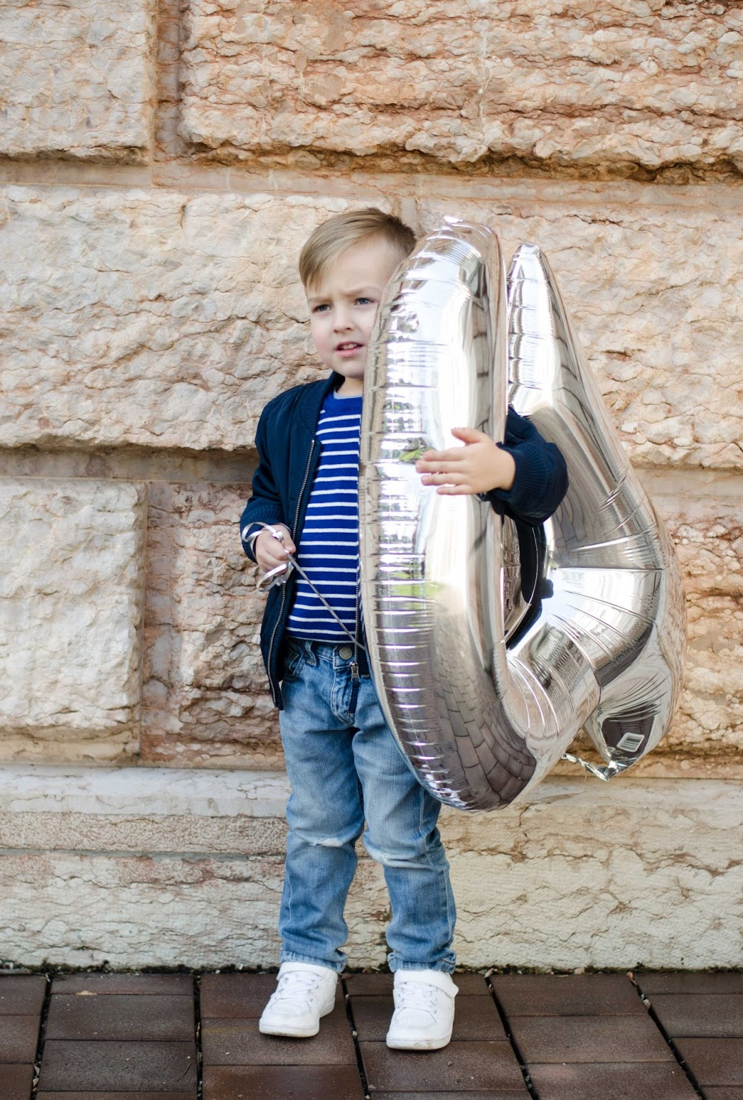 toddler boy with big silver number 4 birthday balloon