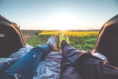 شخصان يجلسان داخل السيارة ويراقبان غروب الشمس