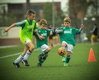 Niños entrenando a futbol sobre hierba en el articulo del plan de apoyo al deporte base