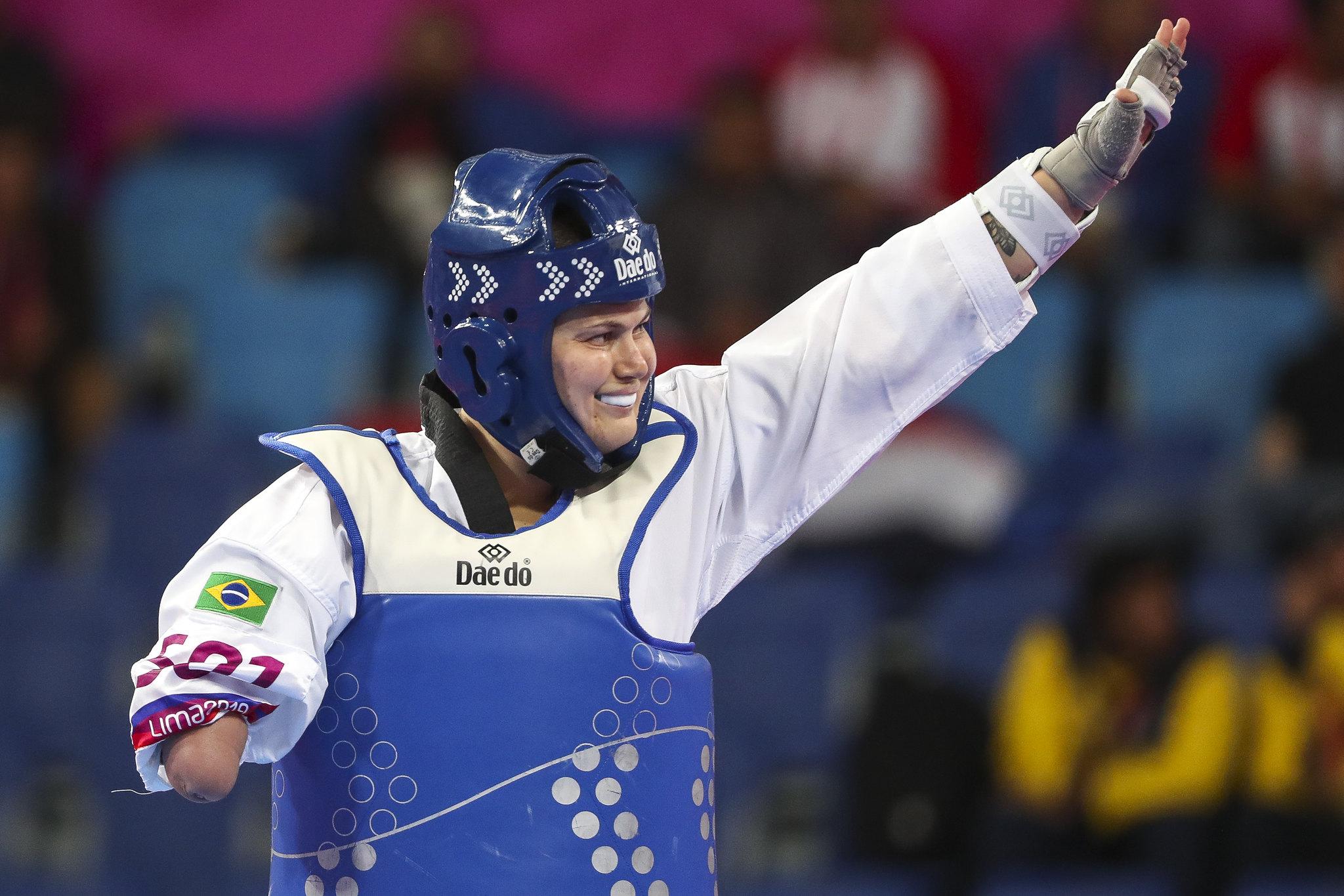 Usando um colete azul, Débora sorri e acena para o público após luta nos Jogos Parapan-Americanos