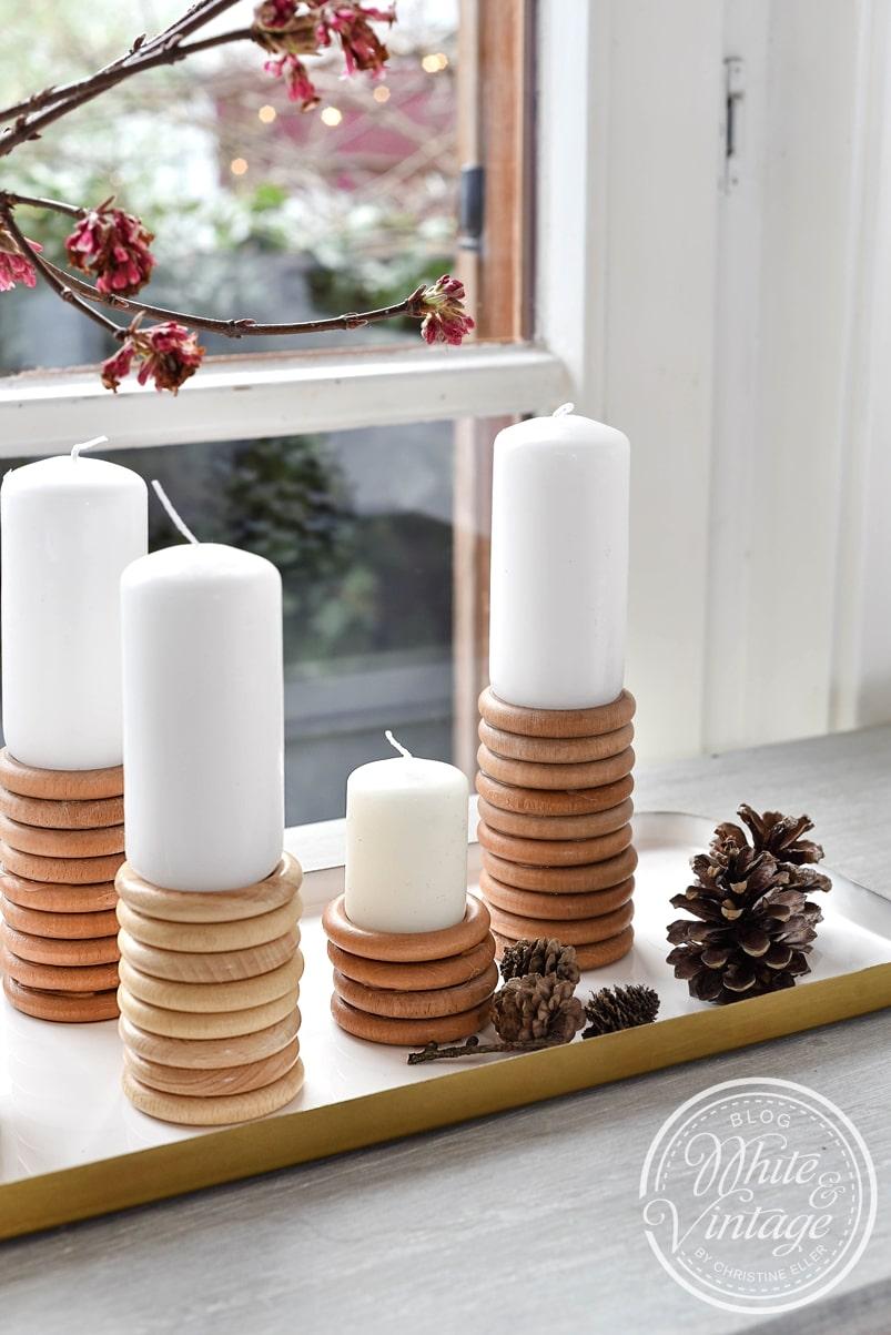 Selbstgebastelte Kerzenständer auf Kerzentablett arrangieren.