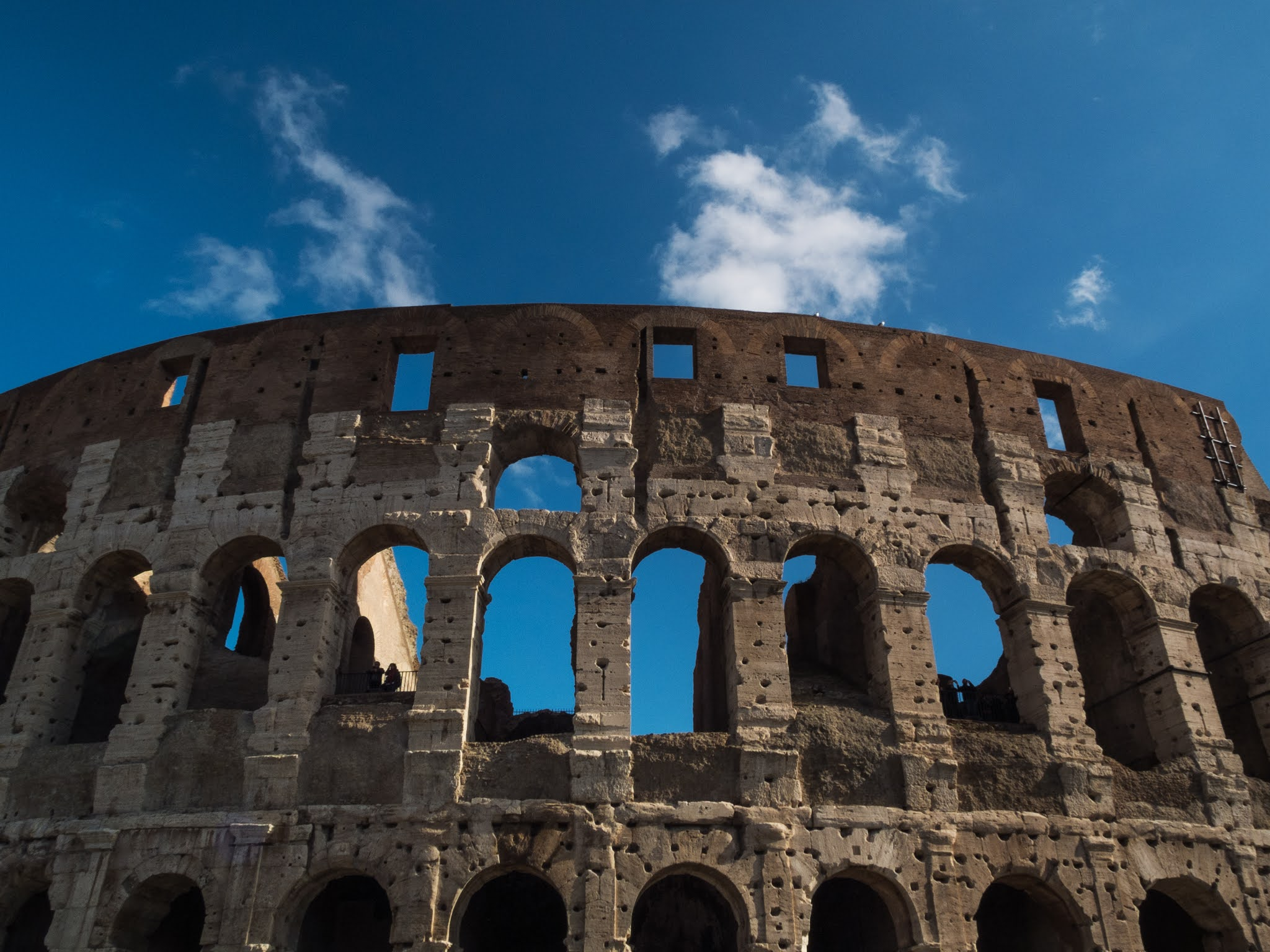 View of the Colosseum against a blue sky.