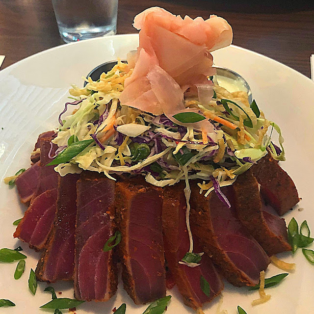 A pyramid of blackened tuna upon a bed of rice topped with a fresh ginger floret and accompanied by slaw.