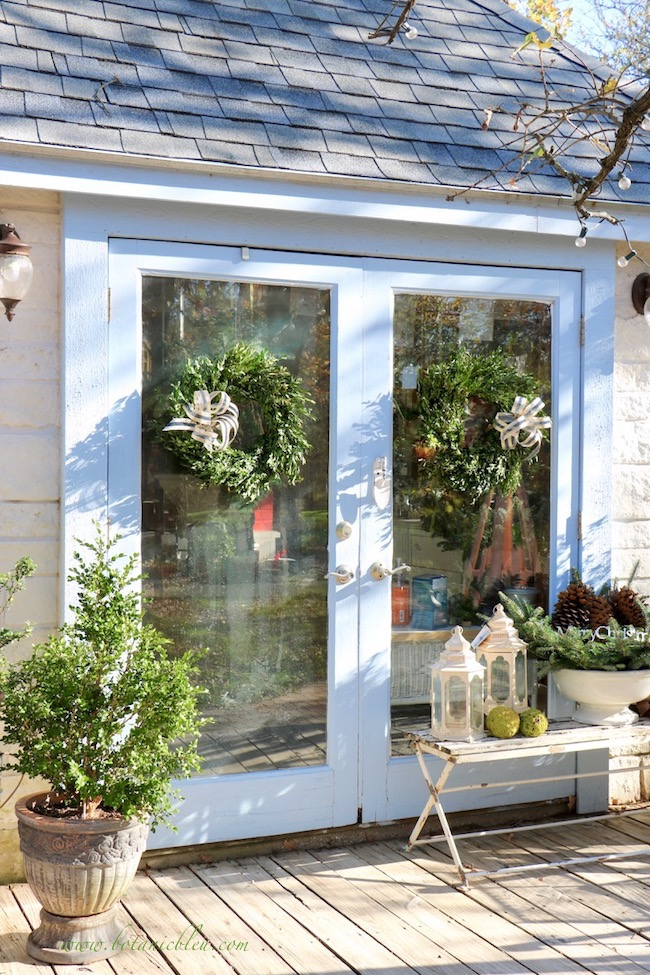 Inexpensive fresh boxwood wreaths hang on the French doors of the French Country Christmas garden shed