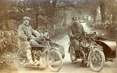 Two men on vintage flat tank motorcycles in cold weather.