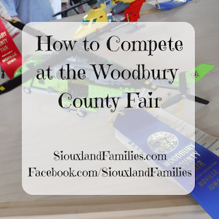"""in background, a lime green lego helicopter has a blue ribbon tied to it from the Woodbury County Fair. In the foregrounds, the words """"how to compete at the Woodbury County Fair"""""""