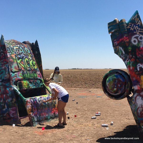 visitor working with spray can at Cadillac Ranch in Amarillo, Texas
