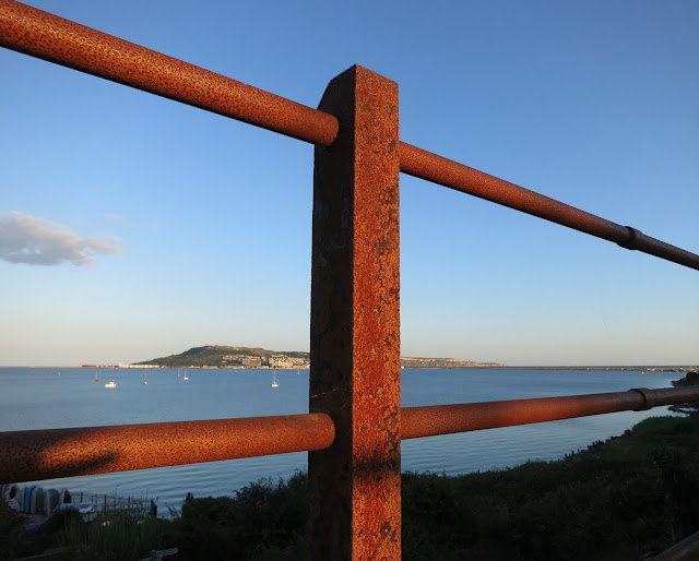 Looking between the rusty railings along an ex-railway bridge with Portland beyond.
