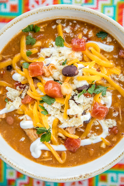 Chicken Tortilla Soup - the secret ingredient makes all the difference!! Ready in about 15 minutes. Can also make this in the slow cooker. Freeze leftovers for a quick lunch or dinner later!! Rotisserie chicken, refried beans, black beans, diced tomatoes and green chiles, taco seasoning, corn and chicken broth. Top soup with cheese, tortilla chips and sour cream. Serve with some cornbread for an easy weeknight meal that the whole family will enjoy! Everyone loved this easy Mexican recipe!!