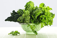 An assortment of leafy greens in a silver colander