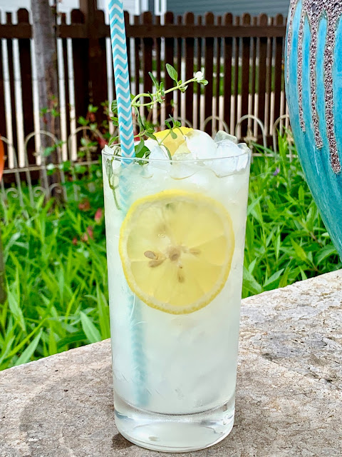 A glass of lemonade, lots of ice, with floating lemon slices and a sprig of thyme sitting on a rock wall in a garden