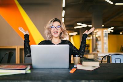 Mulher alegre com braços para cima em frente ao notebook