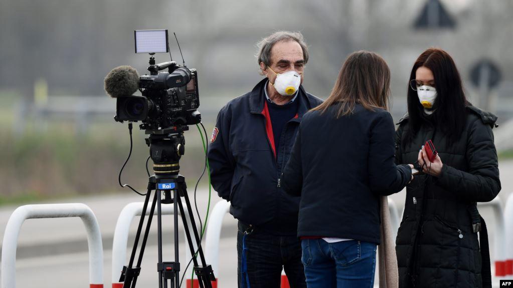 Reporteros usando mascarillas trabajan en la entrada del pequeño pueblo de Casalpusterlengo, en el sudeste de la península italiana, luego que el gobierno impusiera drásticas medidas de contención del brote / AFP