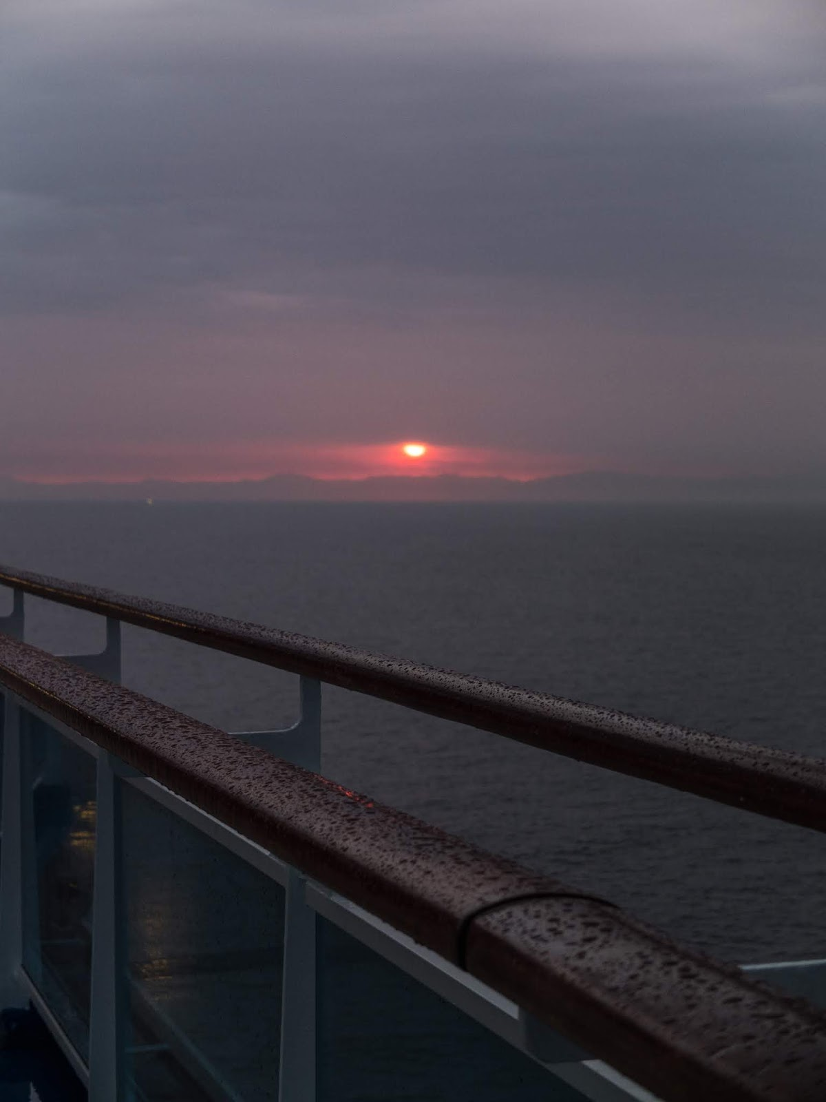 Sun rising over the mountains in the horizon with rain drops on a railing in the foreground.