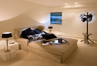 Modern Sofa Bed with Dark Cushions and Pillows near the White Side Tables and Black Shaded Table Lamps