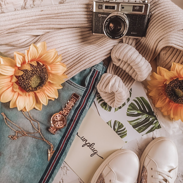 Personal items on a flatlay angle including jeans, a pair of sneakers, camera, sunflowers, a gold watch and necklace, and sweatshirt.