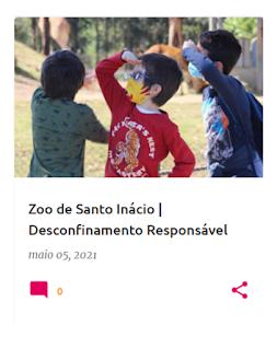 3 crianças com a mão a fazer pála em cima dos olhos, a olhar cada um para seu lado, com girafas ao fundo