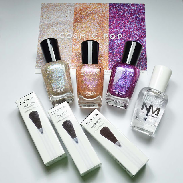 Zoya nail polish bottles and wide brushes arranged in a flat lay
