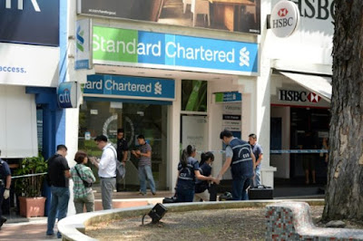 Singapore police investigate a crime scene in front of a Standard Chartered bank branch