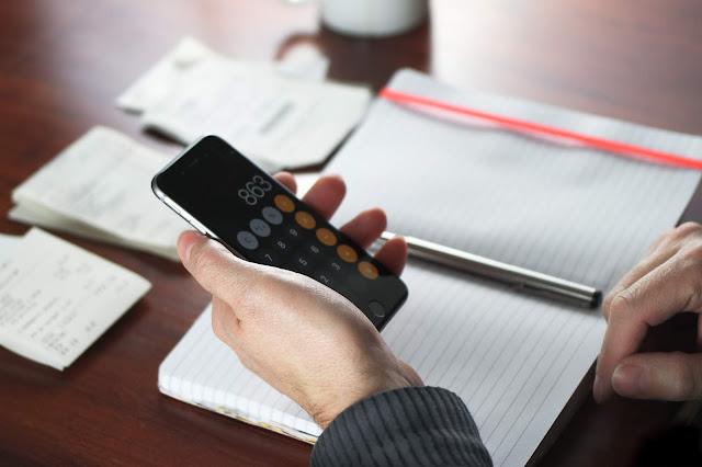 Mãos masculinas segurando celular com calculadora sobre a mesa