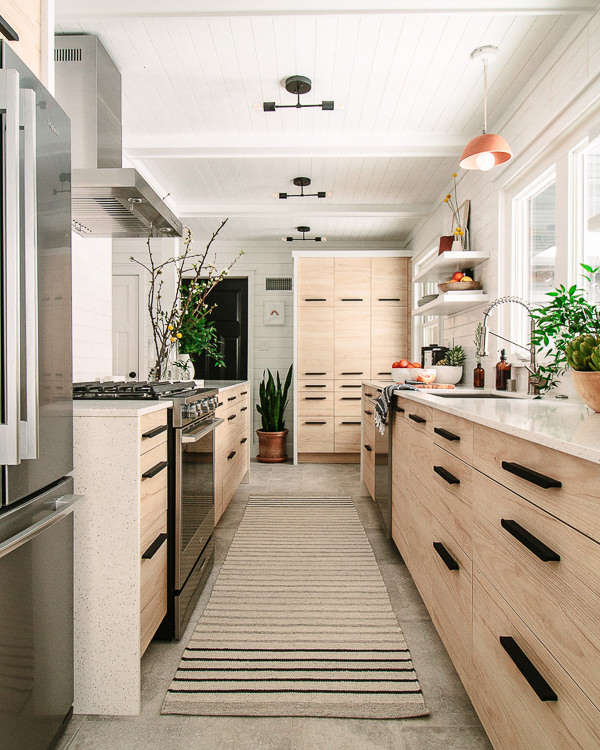 galley kitchen with light wood cabinets