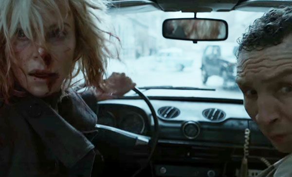Lorraine (Charlize Theron) and Spyglass (Eddie Marsan) during a car chase scene in ATOMIC BLONDE (2017)