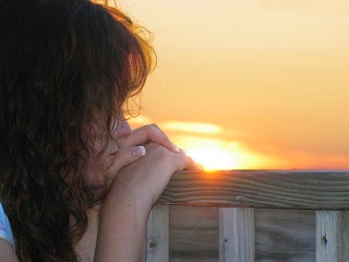 A lady daydreaming as she watches the sunset in the background.