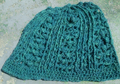 A crochet hat done in dark teal fingering-weight yarn; with columns of bobbles and raised post stitches.