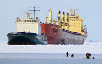 The Mudyug icebreaker, left, leads a ship named the Federal Danube as men fish in the frozen Gulf of Finland, some 25 miles west of St. Petersburg, Russia, Tuesday, March 15, 2011. (Credit: Dmitry Lovetsky / AP) Click to Enlarge.