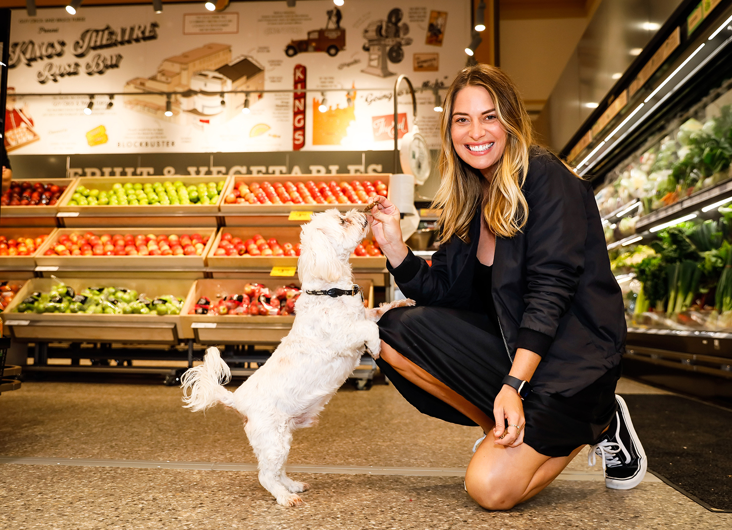Young woman kneels down to feed a treat to a Maltese Shih Tzu dog at Coles Rose Bay