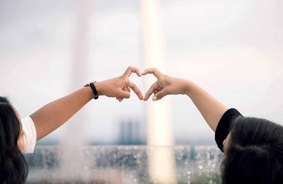 صديقات يعملون حركة القلب بالأيدى بأيديهم
