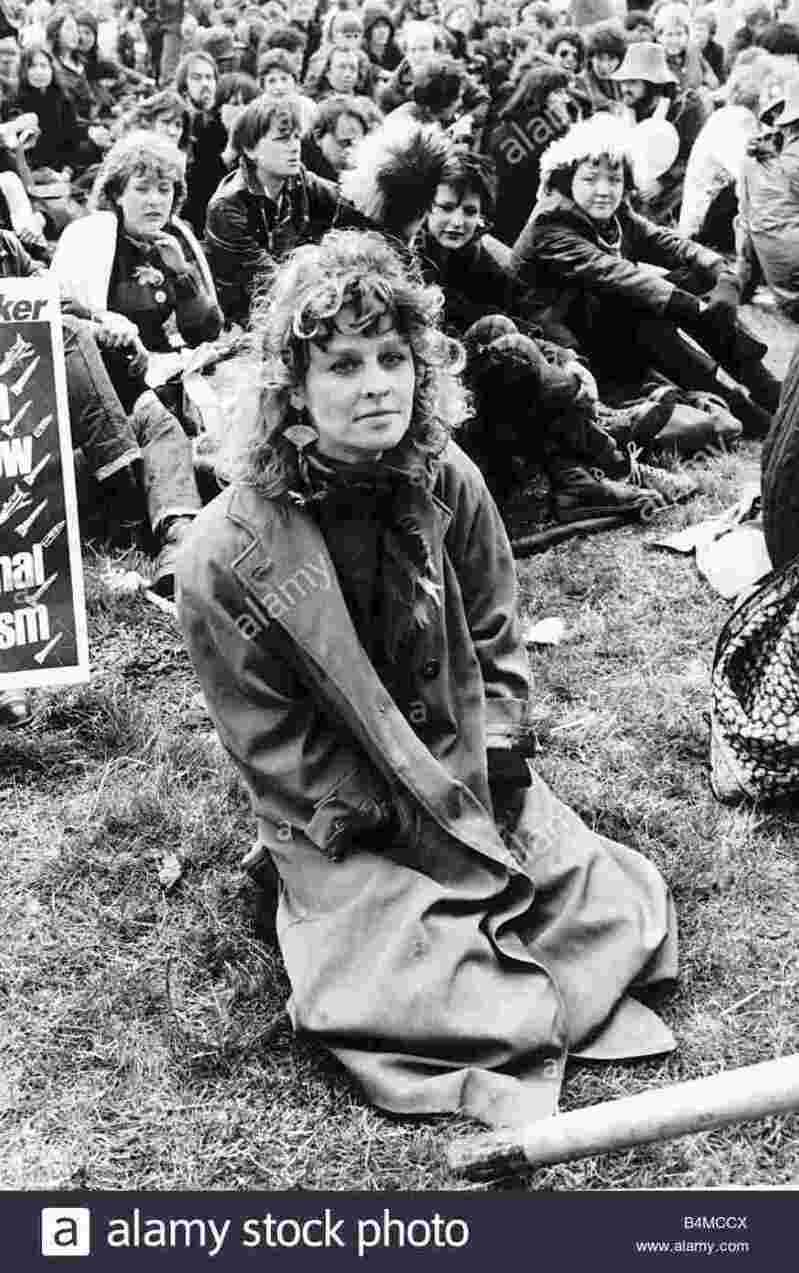 Julie Christie sitting on grass at Greenham Common