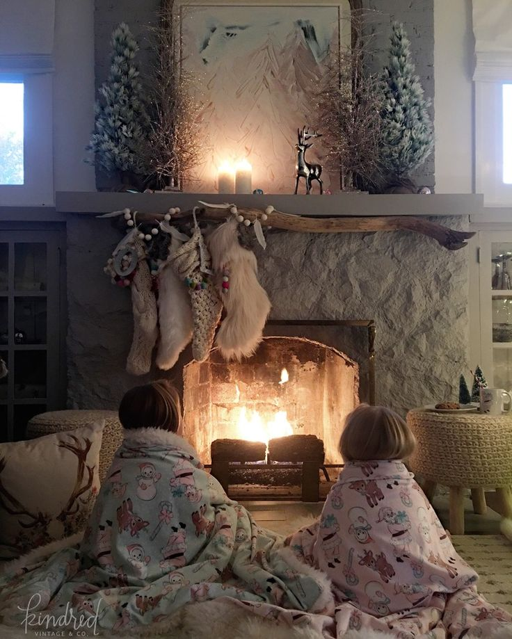 Children wrapped in blankets in front of fire in room with Farmhouse Christmas holiday decorating shabby chic