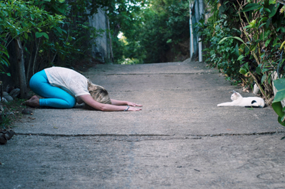 woman and cat doing yoga pose outdoors