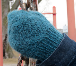: Someone wearing a cabled mitten and gripping a chain. The mitten cables enclose a section of double moss stitch.