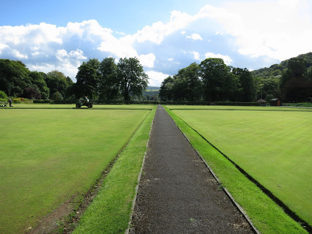 Path between bowling greens with park-keepers mowing the grass in Todmorden, West Yorkshire