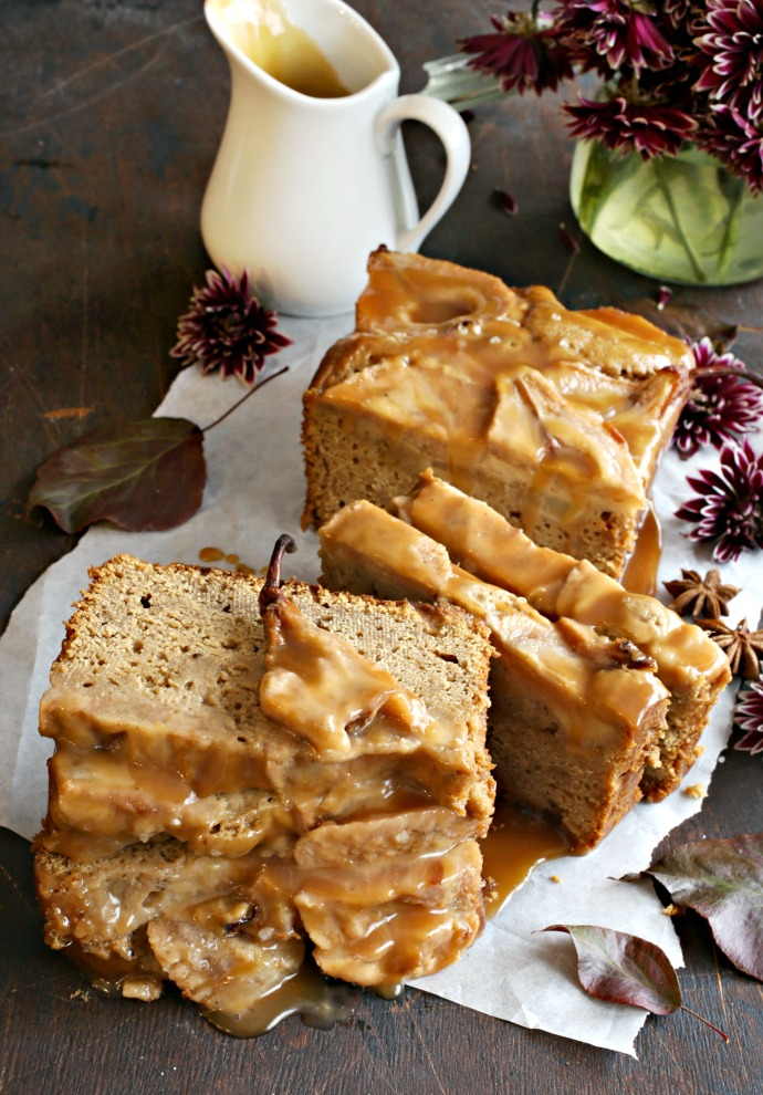 Recipe for a gingerbread loaf cake topped with thinly sliced baked pears and drizzled with homemade salted caramel sauce.