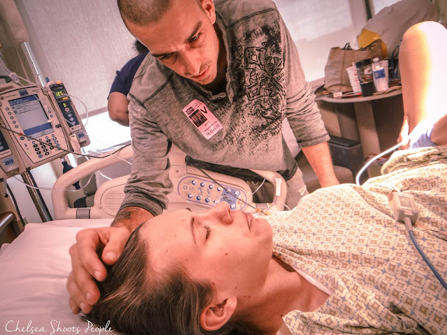 Father rubs mother head and hair while she is having a contraction. Photography.