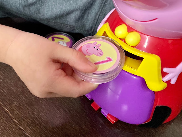 Close up of a preschooler hand pushing a coin into Count with Peppa