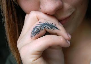 tatuaje pluma pavo real dedo
