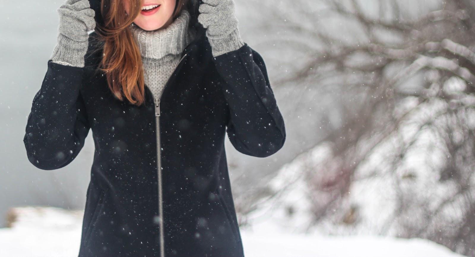 小雪が舞う中で紺色のコート着てフードを被っている女性