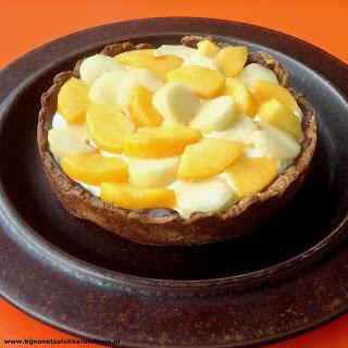 zelfgebakken taartje met gele en witte perzik bovenop