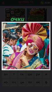 женщина в цветной одежде с бантом на голове и в очках зеркальных
