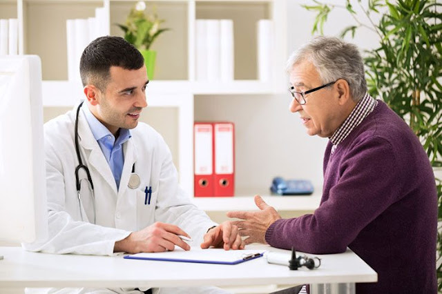 Image of an older man discussing his neuropathy signs and symptoms with a doctor.