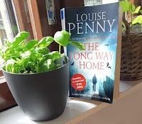 Kirja ikkunalaudalla, edessä kasvaa basilikaa ruukussa ja takana paprikantaimia
