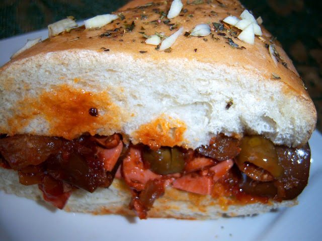 this is a fried bologna and eggplant appetizer sandwich with olives and sauce in a hard crusted Italian roll. This is on a dish by a picture window.