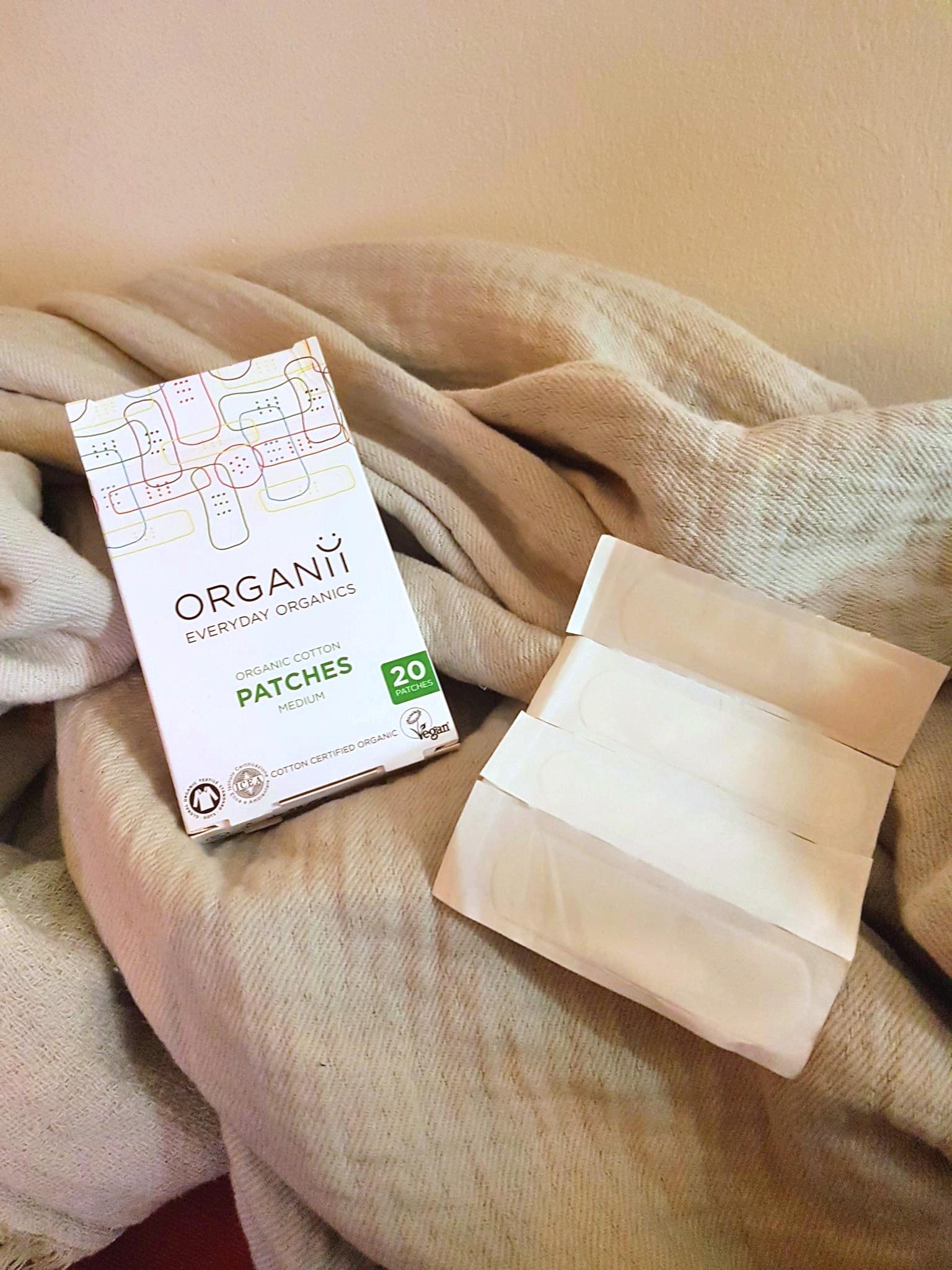box of organic cotton plasters sitting on light blue throw blanket