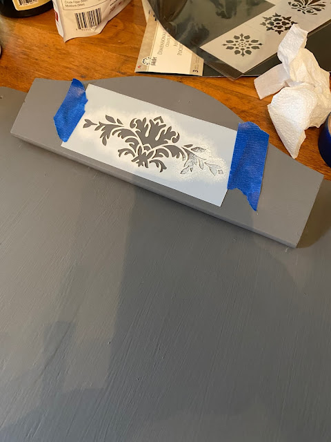 Photo of a wooden clip being stenciled with white paint